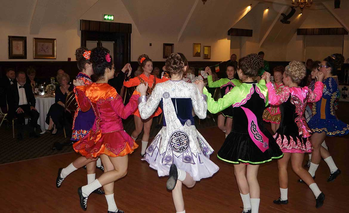 Irish society watching children dance at an event in Norwich